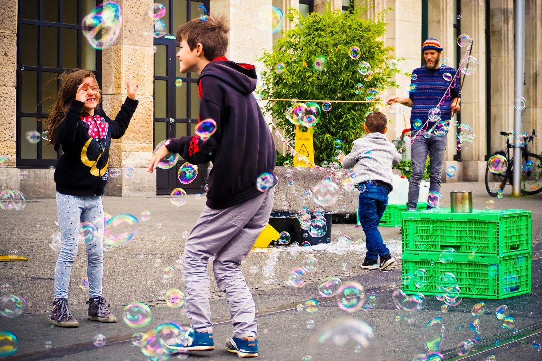 Children playing with bubbles in an urban setting